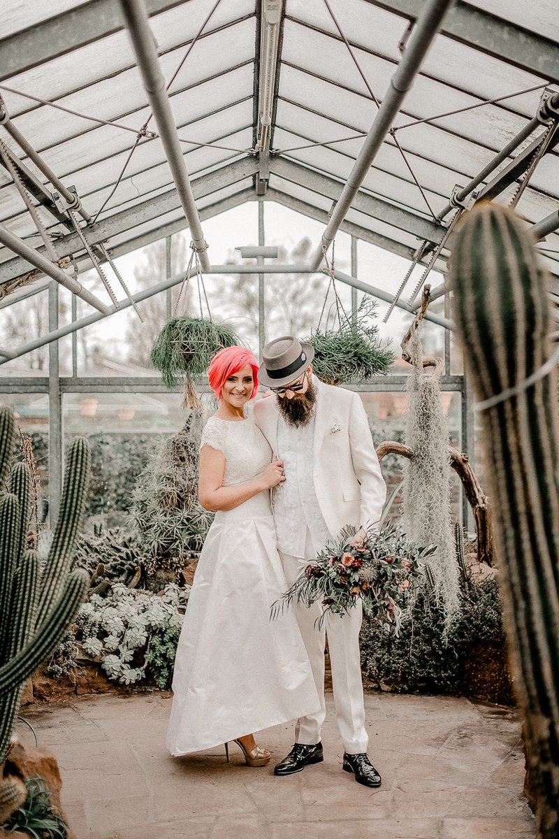 Bride with pink hair and groom in white suit and hat