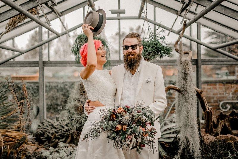 Bride taking hat off of groom's head