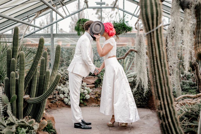 Bride holding groom's hat in front of their faces as they kiss