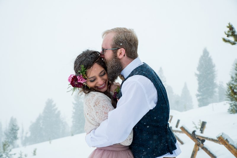 Groom kissing bride on side of head in the snow