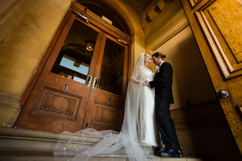 Bride and groom standing by entrance to Heythrop Park