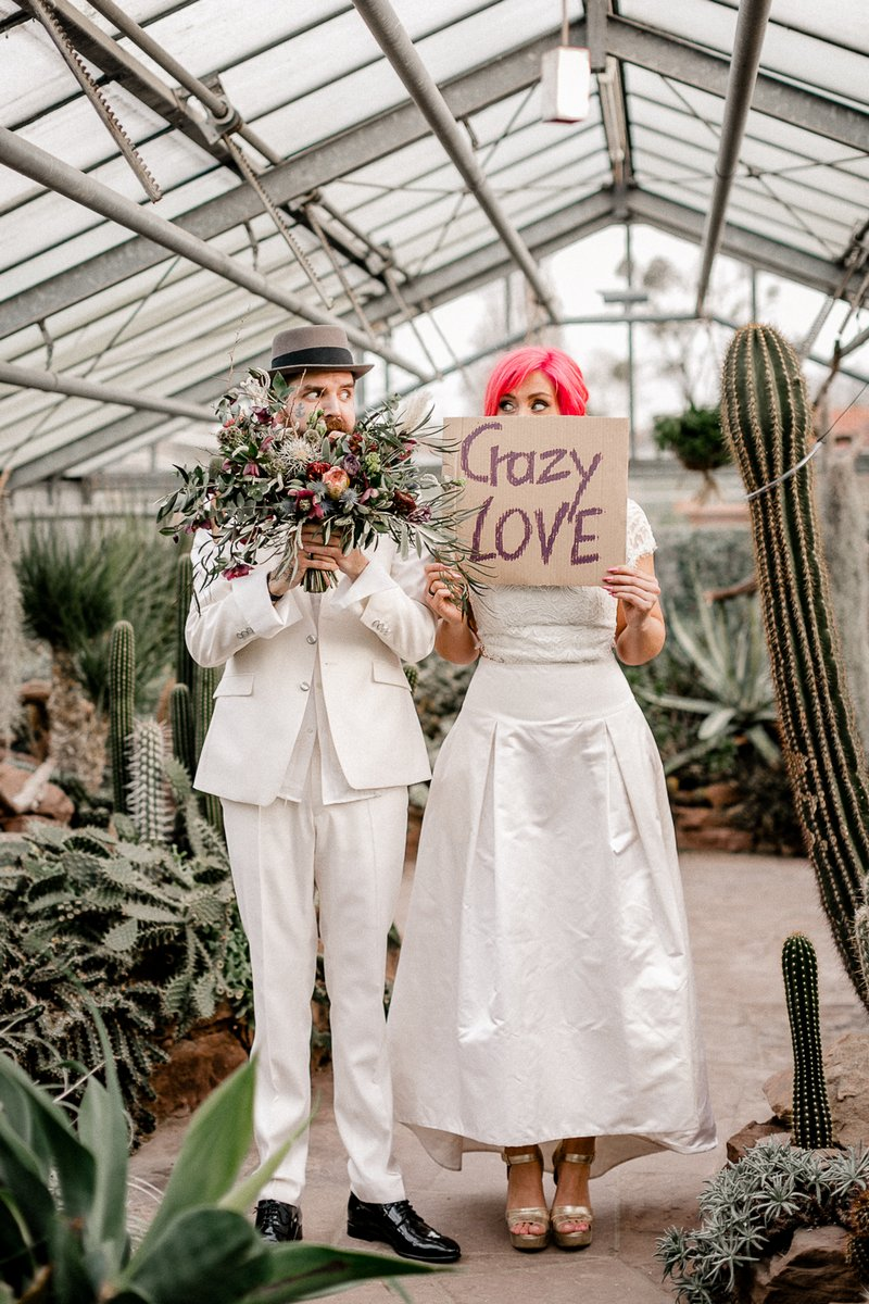 Groom holding bouquet and bride holding crazy love sign