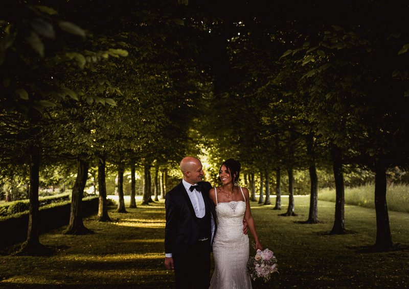 Bride and groom walking diown tree lined road