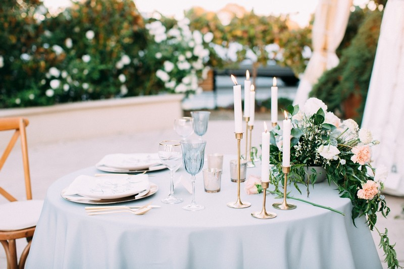 Small wedding table with dusty blue tablecloth and elegant styling