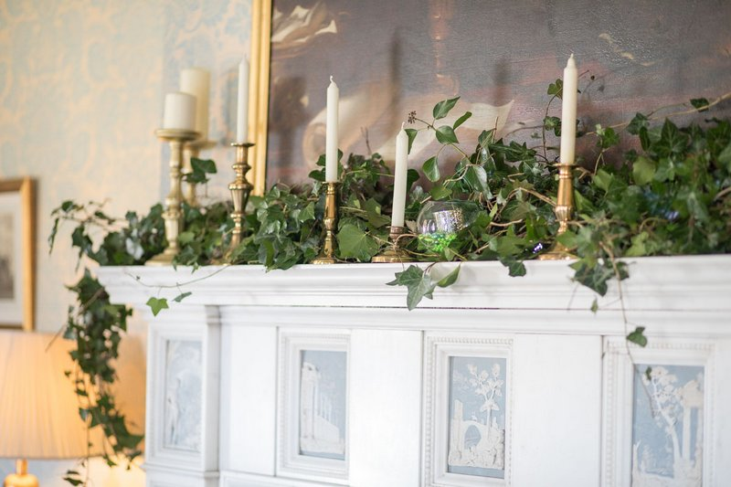 Foliage and candles on fireplace at Heythrop Park