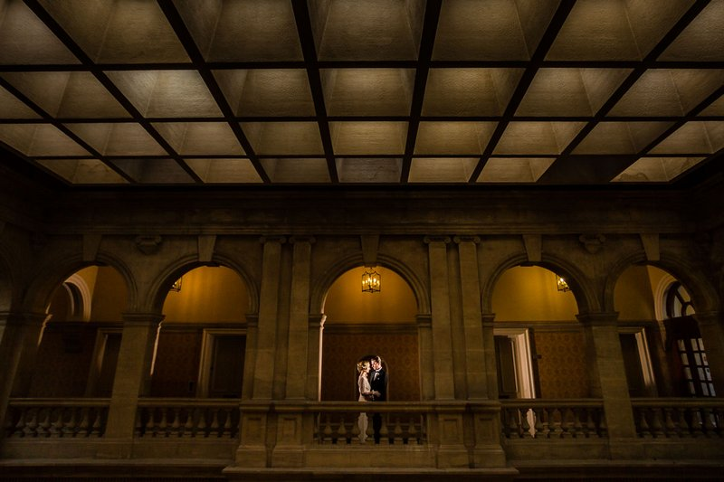 Bride and groom standing on gallery of Heythrop Park