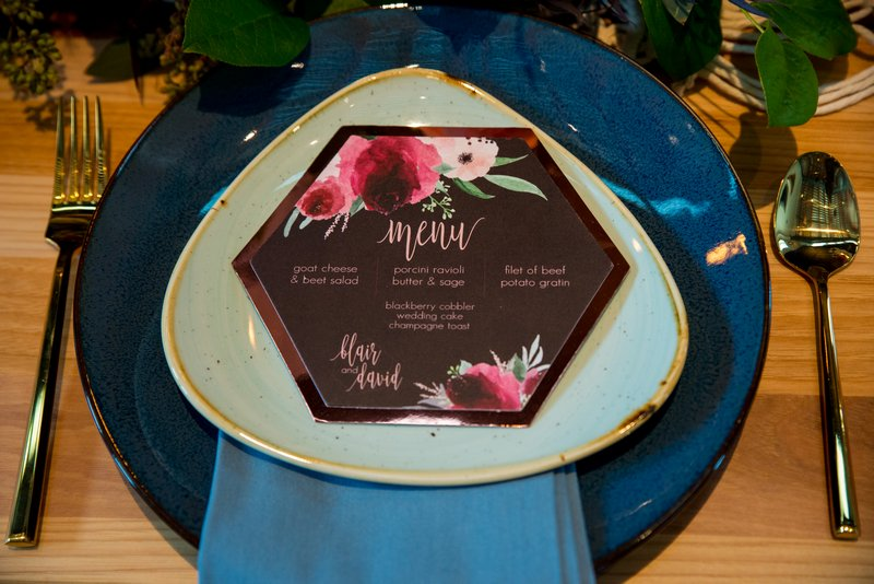 Purple wedding menu on blue charger plate
