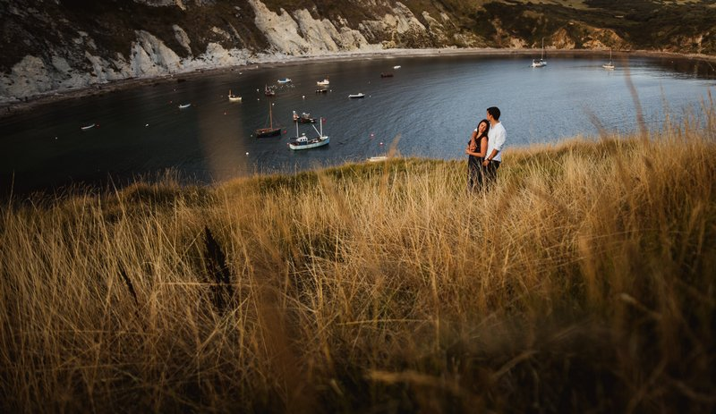Couple on bank by water and cliffs
