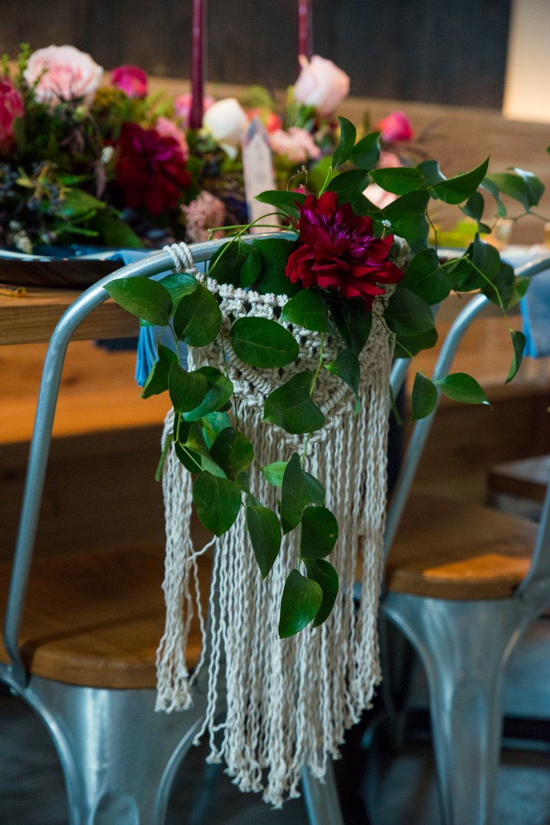 Macramé and flowers on back of wedding chair