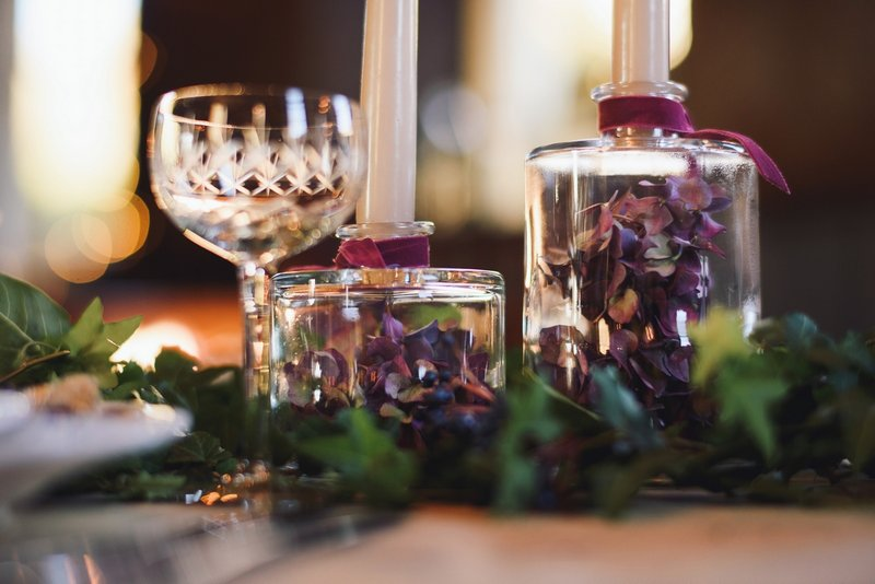Purple hydrangea petals in bottle candle holder