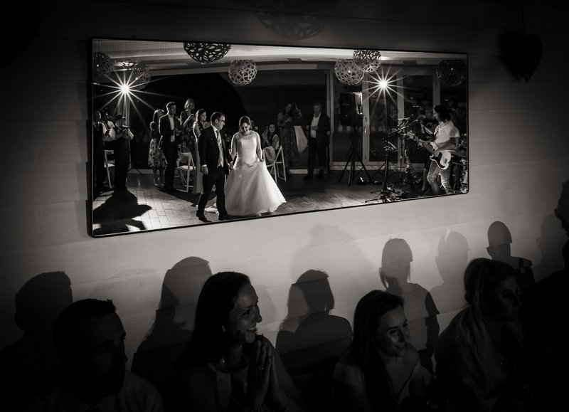 Reflectiojn in mirror of bride and groom walking onto dance floor