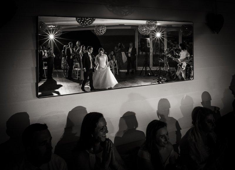 Reflectiojn in mirror of bride and groom walking onto dance floor