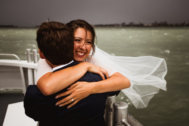 Bride and groom hugging on boat