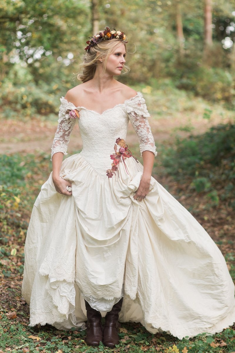 Bride wearing silk wedding dress with embroidered leaves and flowers