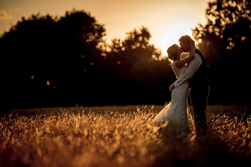 Bride and groom kissing in field as sun sets