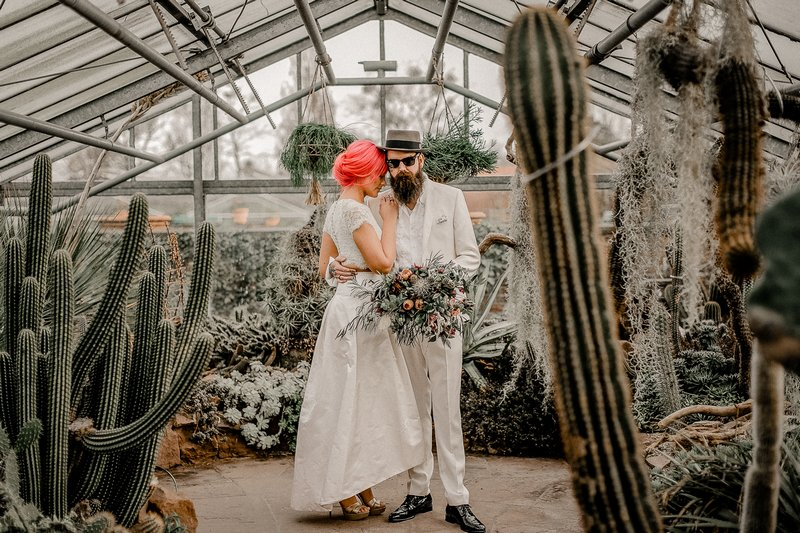 Bride and groom in greenhouse full of cactuses