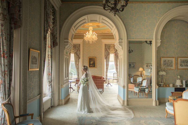 Bride looking out of window of Heythrop Park