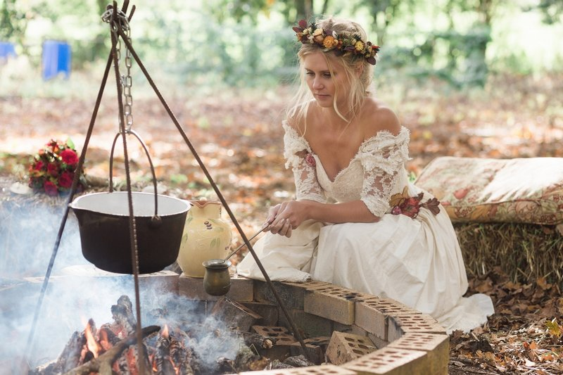 Bride holding pot over open fire in woodland