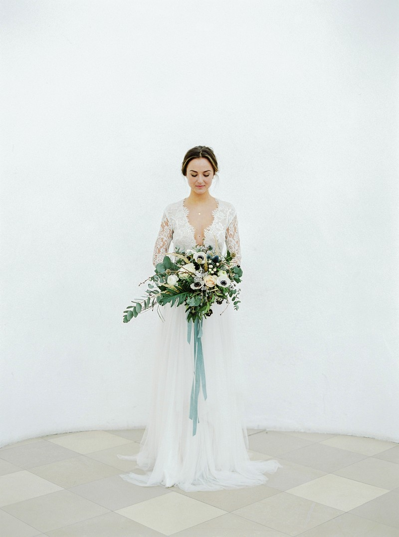 Elegant bride standing holding bouquet