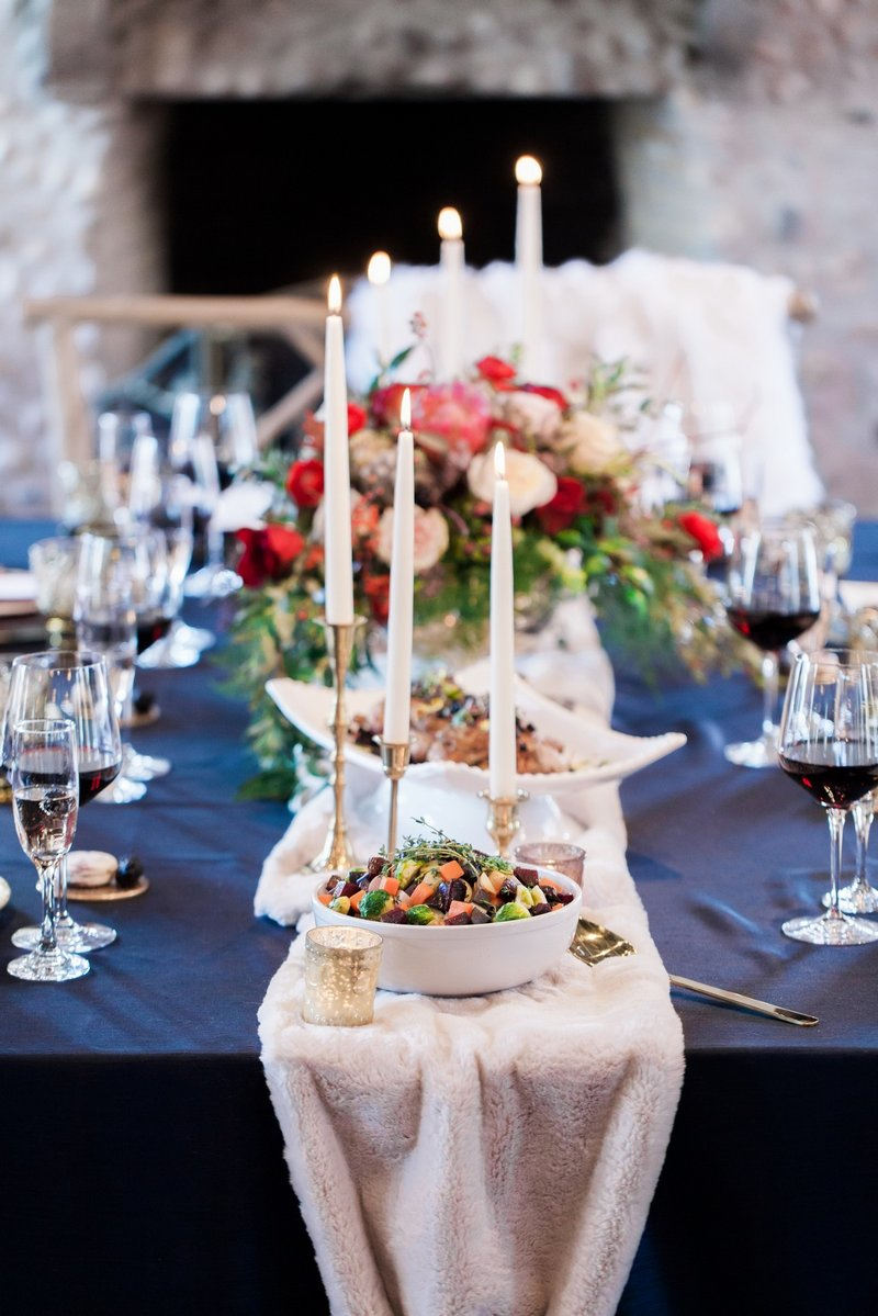 Candles and food on top of white fur wedding table runner