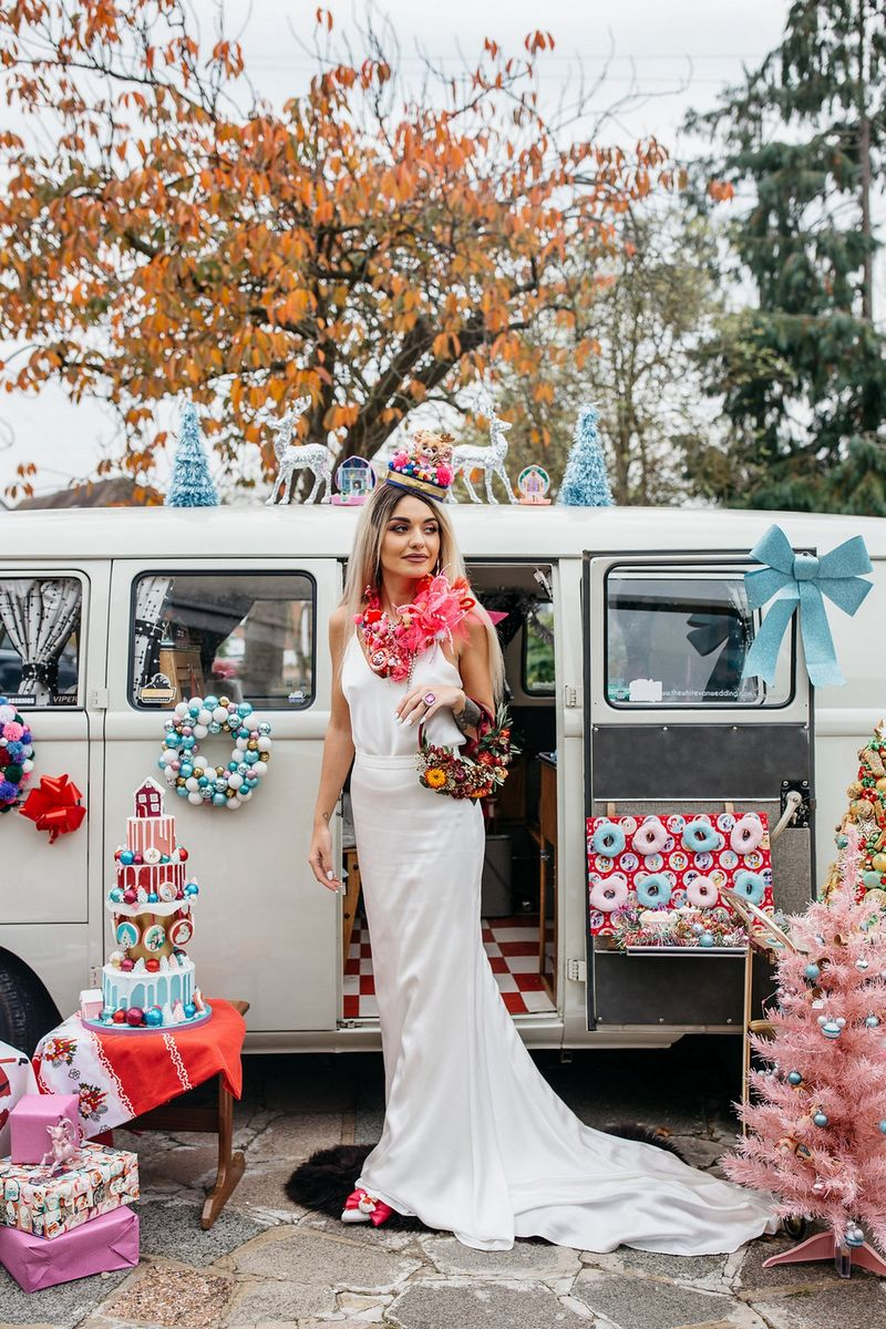 Bride outside VW camper van surrounded by kitsch Christmas props