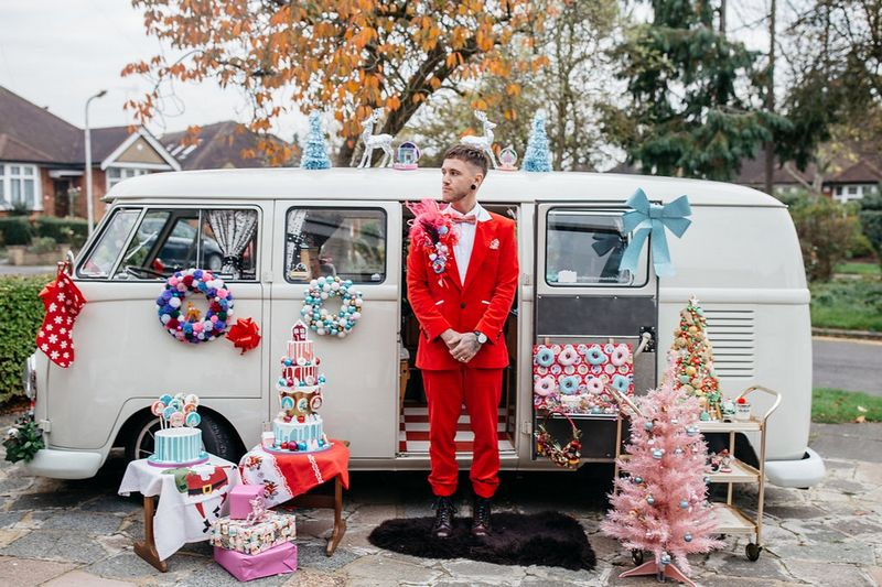 Groom in red suit standing outside VW Camper Van surrounded by Christmas kitsch items