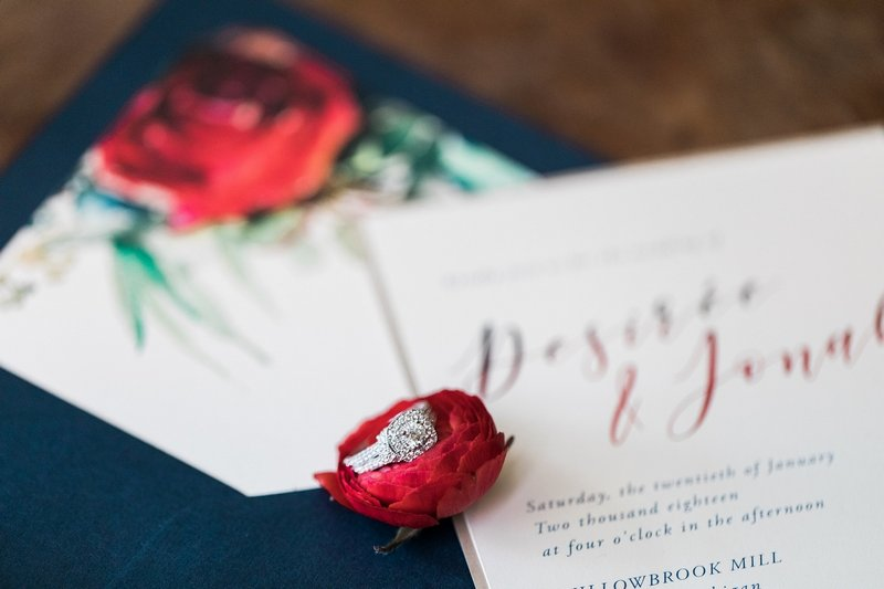 Wedding ring on red flower on top of wedding stationery