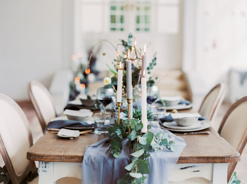 Candles and foliage on grey table runner