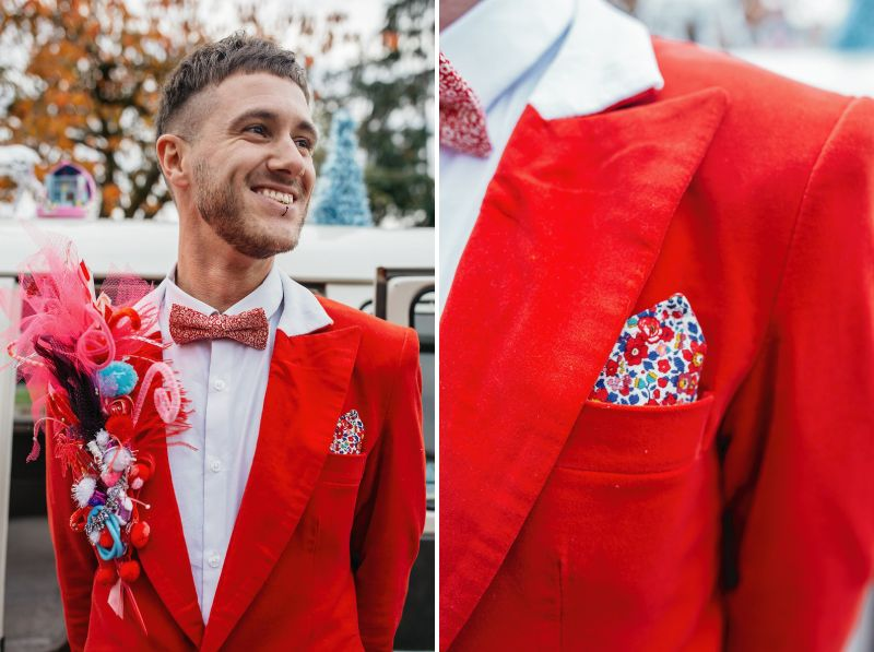 Groom wearing red suit with colourful pocket square and lapel piece