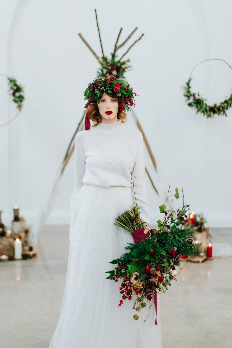 Bride wearing foliage and red berries crown carrying winter wedding bouquet