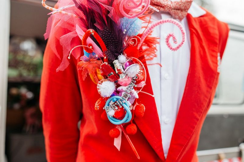 Red lapel piece made from pom poms, pipe cleaners and toys