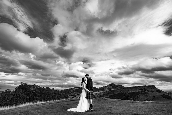 Bride and groom facing each other with dramatic clouds overhead - Picture by Ashley-Liv Jamieson Photography