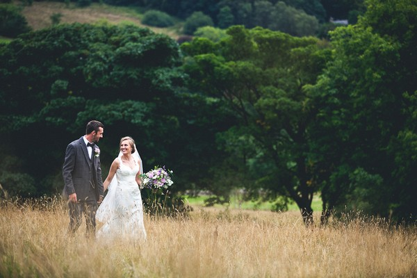 Bride and groom holding hands walking through field - Picture by Katie Sidell Photography