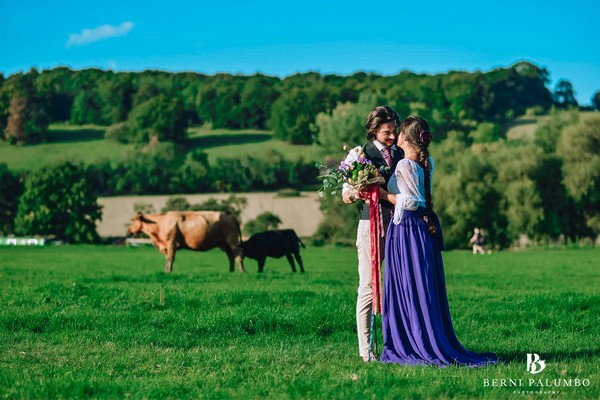 Groom standing with bride in purple skirt in field with cows - Picture by Berni Palumbo Photography