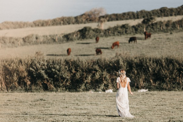 Boho bride walking across field - Picture by Ben Wigglesworth Photography