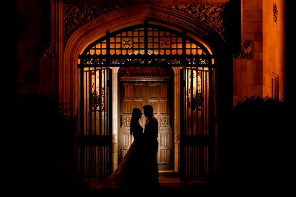 Bride and groom standing at gated good of wedding venue at night - Picture by Damion Mower Photography