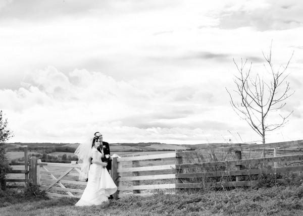 Bride and groom standing by gate to field in countryside - Picture by Rosie Cutbill Photography