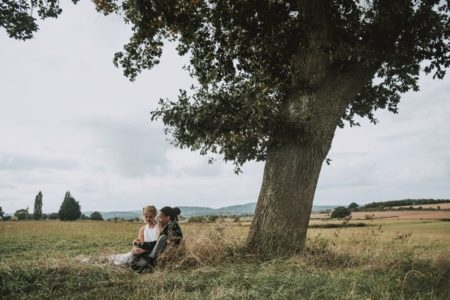 Bride and groom sitting under tree - Picture by Chivers Weddings