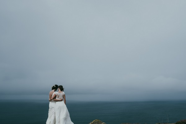 Two bride standing looking looking out to sea - Picture by Ross Talling Photography