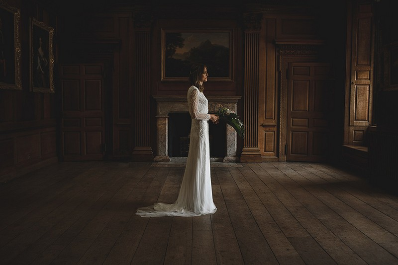 Bride standing holding bouquet in middle of room - Picture by Rik Pennington Photography
