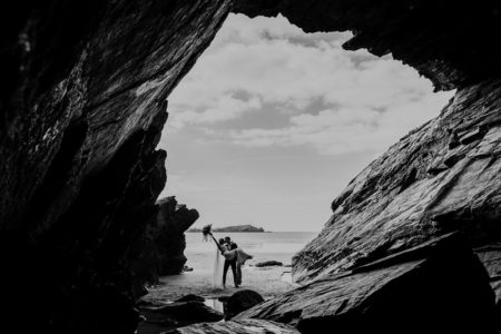 Picture taken from cave of bride and groom kissing on beach - Picture by Alexa Poppe Wedding Photography