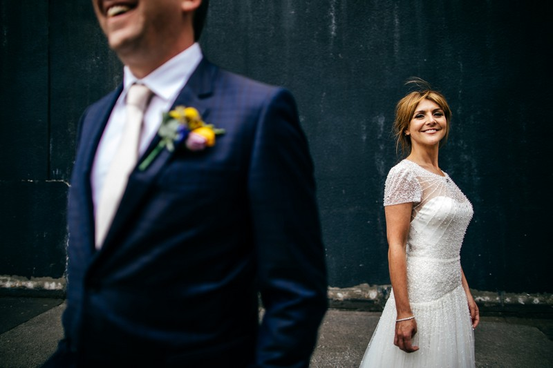 Bride in background smiling with groom in foreground - Picture by Jordanna Marston Photography