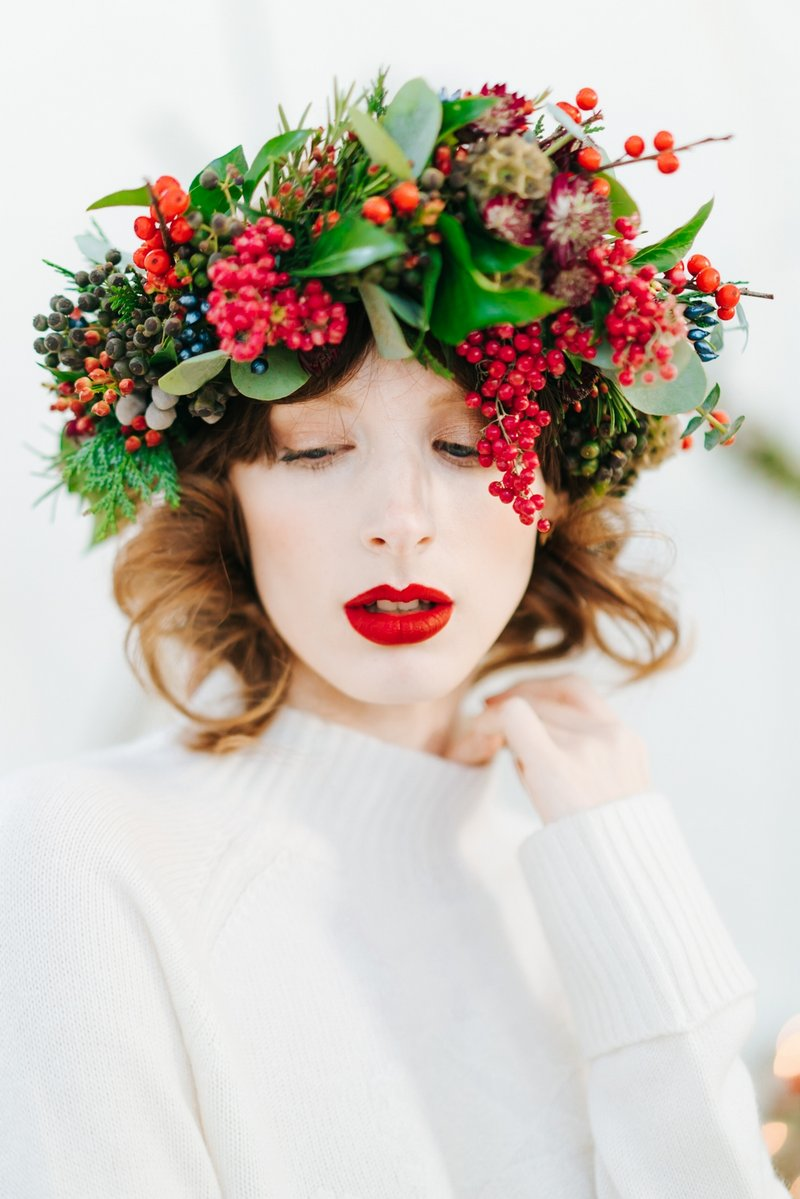 Bride with red lipstick and green foliage and red berry crown