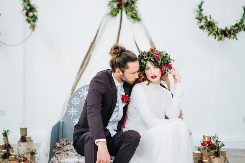 Winter bride and groom sitting on sleigh