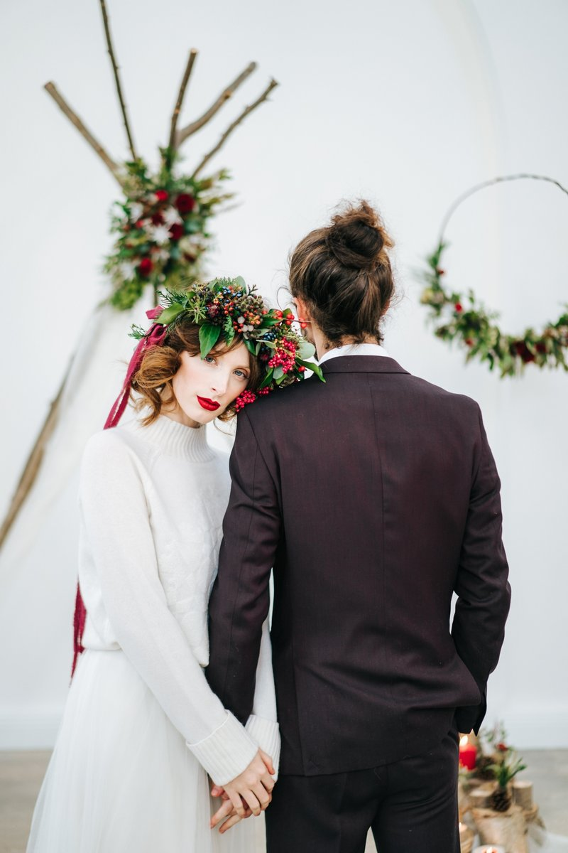 Bride with red berry and foliage crown holding groom's hand