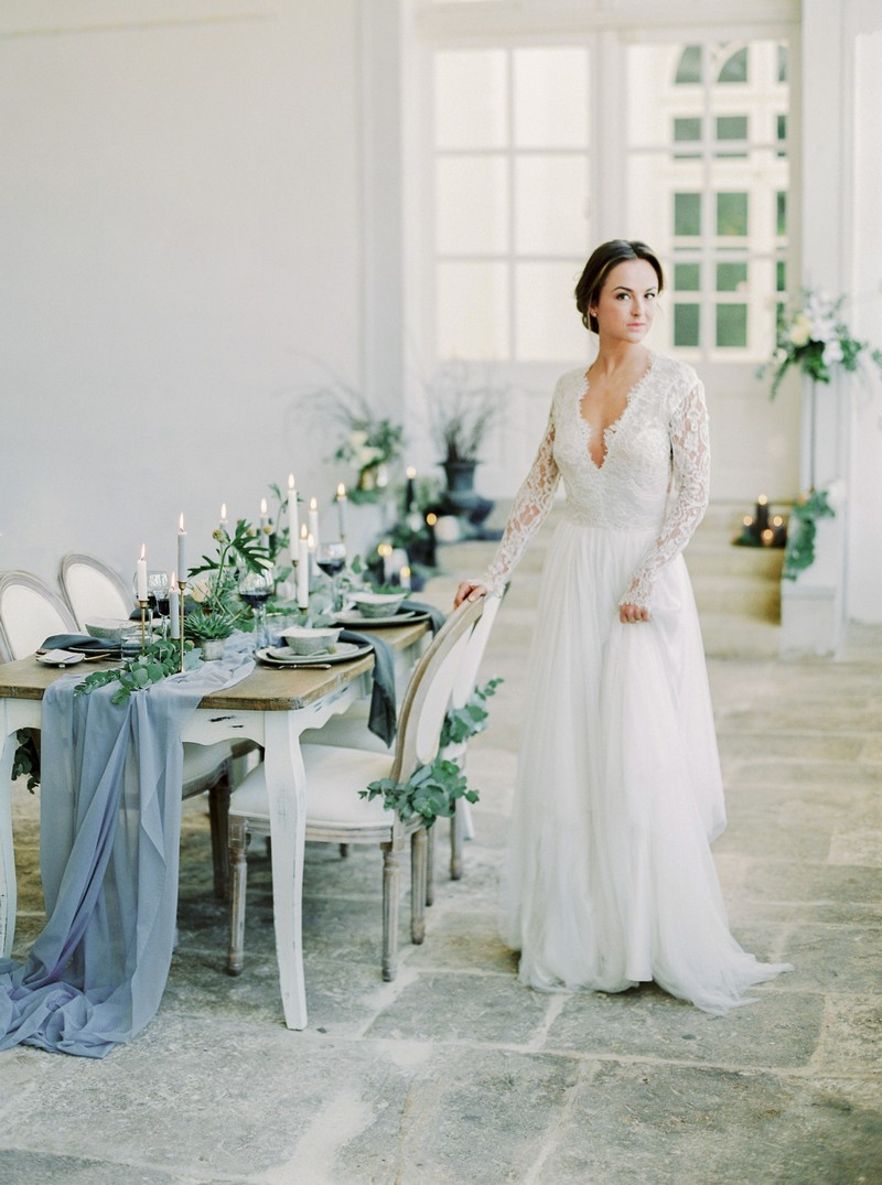 Elegant bride standing next to wedding table with grey styling