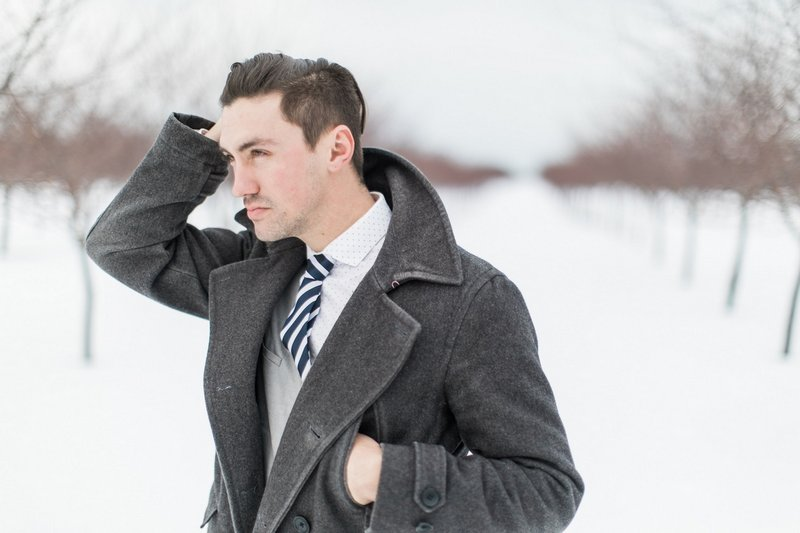 Groom with long coat in snow