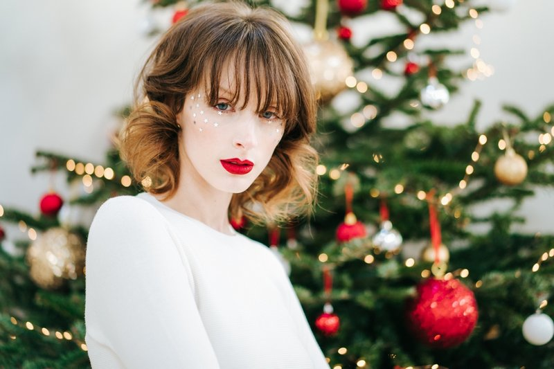 Bride with fringe hairstyle standing in front of Christmas tree