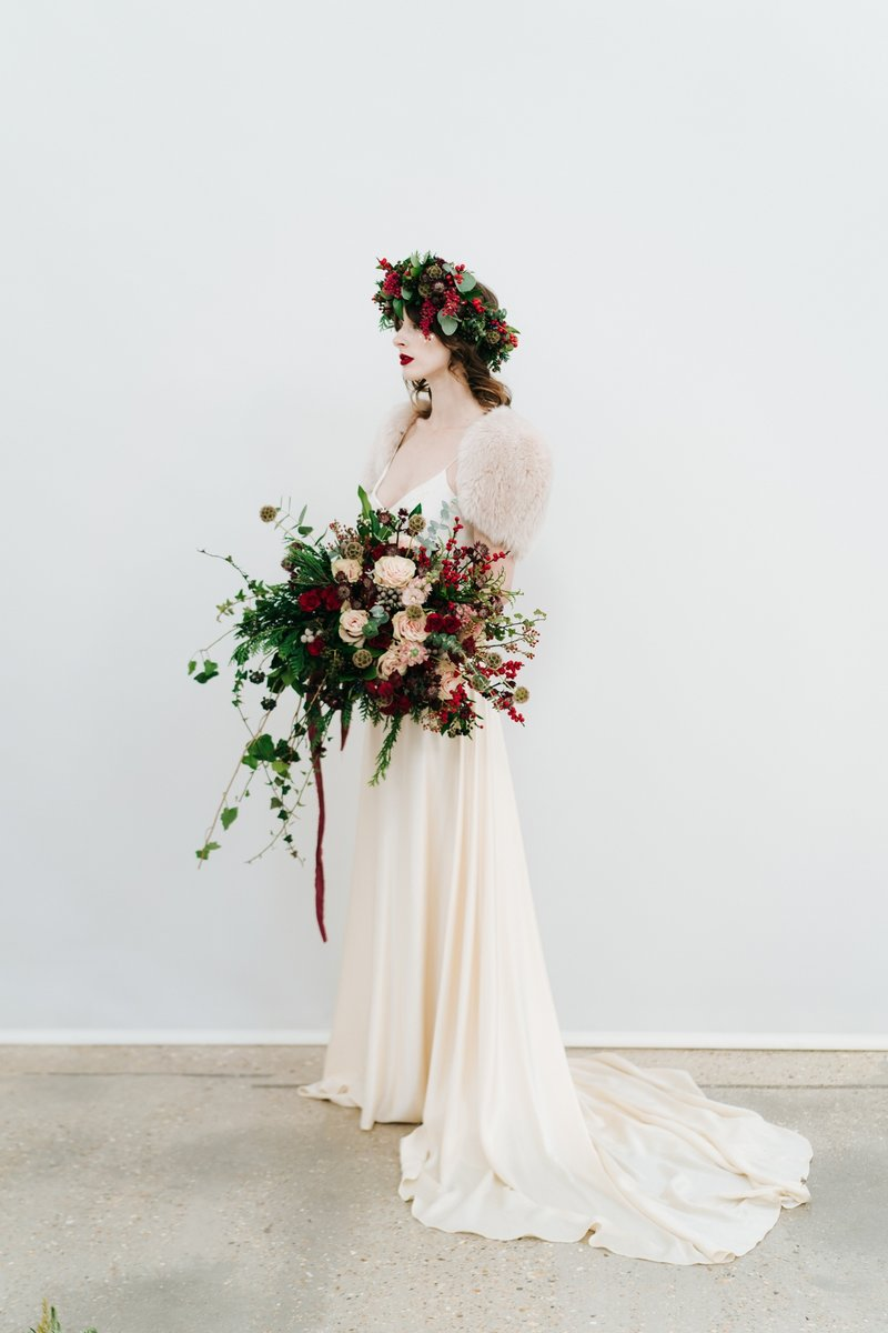 Bride with red berry and foliage crown holding large winter wedding bouquet