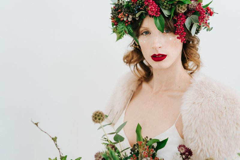 Winter bride wearing foliage and red berry crown and holding bouquet